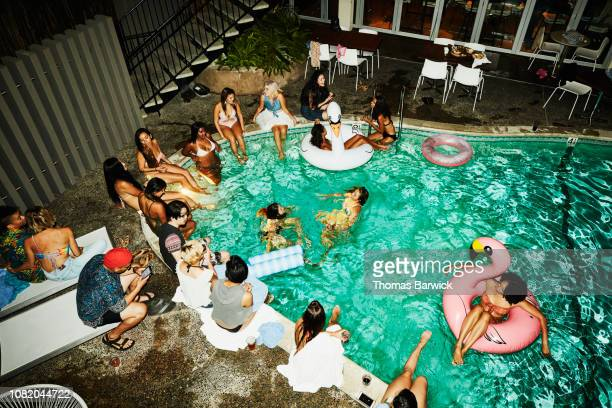 overhead view of party at hotel pool - pool party stock pictures, royalty-free photos & images