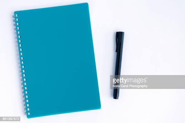 Overhead View of Pen and Blue Note Pad on White Background