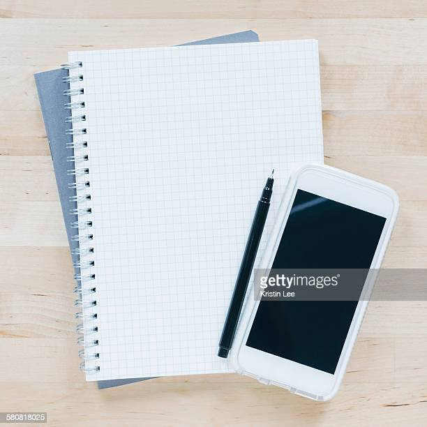 Overhead view of pen and smart phone on notebook