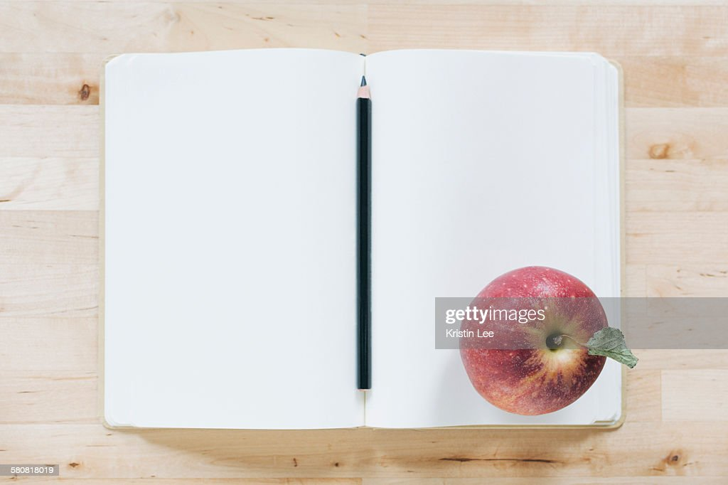 Overhead view of pencil and apple in notebook : Stock Photo