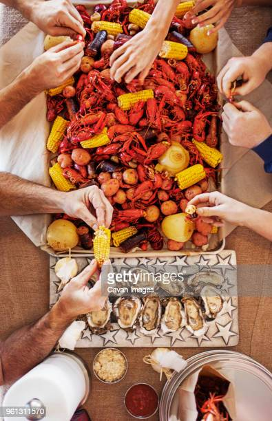 overhead view of people eating a crayfish boil with potatoes, corns and oysters at dining table - boiled stock pictures, royalty-free photos & images