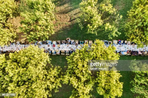 overhead view of people having food at outdoor dining table - abundance stock pictures, royalty-free photos & images