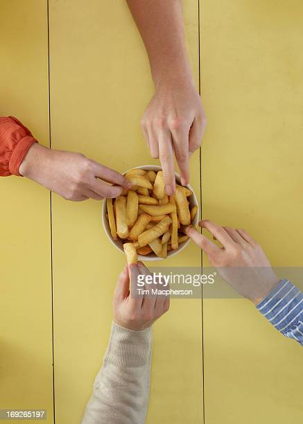 overhead view of people sharing fries - fries imagens e fotografias de stock