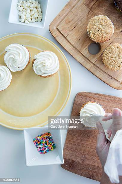 Overhead view of person icing cupcake