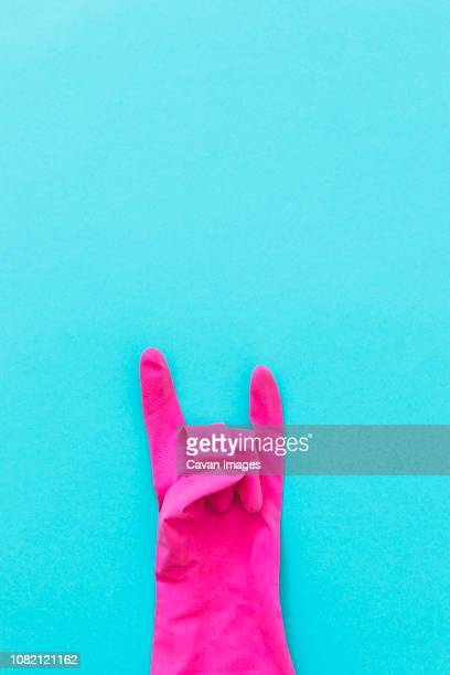 overhead view of pink glove with horn sign on blue background - ゴム手袋 ストックフォトと画像