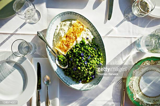Overhead view of plate of english peas on table