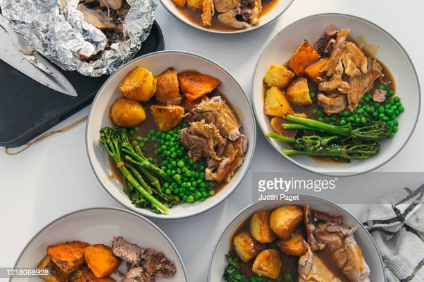overhead view of plates served up with roast pork and trimmings - roast dinner stock pictures, royalty-free photos & images