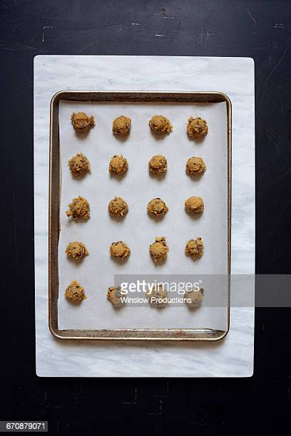 Overhead view of portions of chocolate chip cookie dough on baking sheet