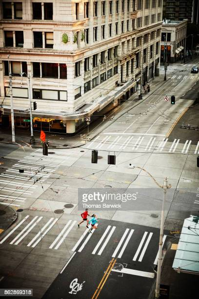Overhead view of pregnant woman and husband on early morning run on city street