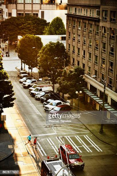 Overhead view of pregnant woman and husband running together on city street during early morning workout