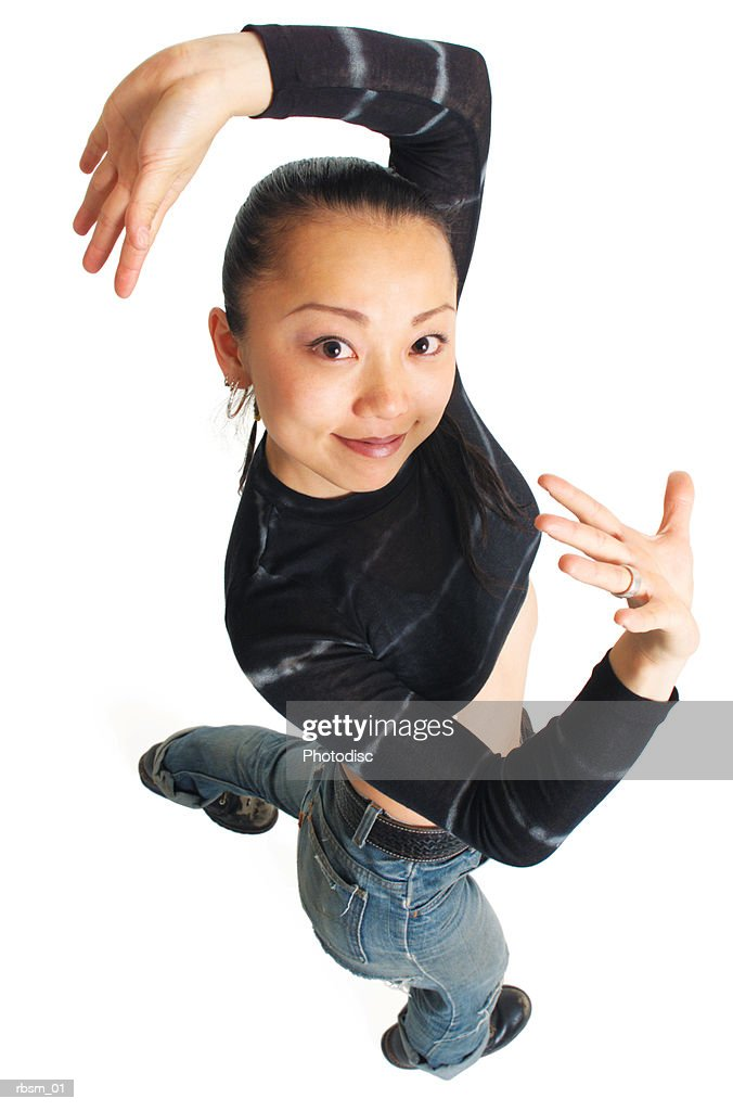 overhead view of pretty young asian girl in jeans and black tye-dye shirt raising her arms and dancing as she looks up into the camera : Foto de stock