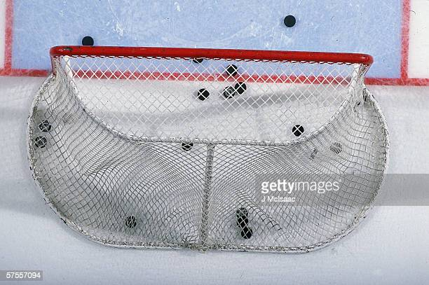Overhead view of pucks in and around the goal net on an ice hockey rink November 2001