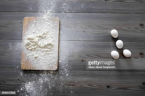 Overhead view of raw eggs and flour on kitchen table