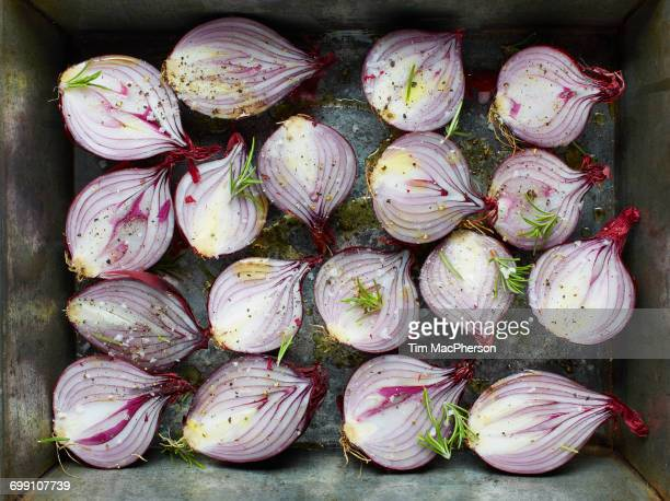 Overhead view of red onion halves with rosemary and olive oil in roasting tin