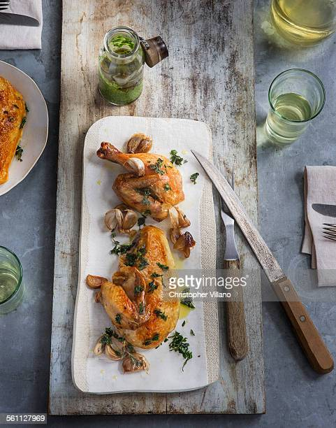 Overhead view of roasted chicken with herb garnish