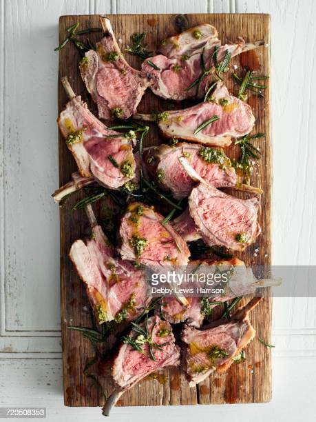 Overhead view of roasted lamb cutlets on cutting board with rosemary