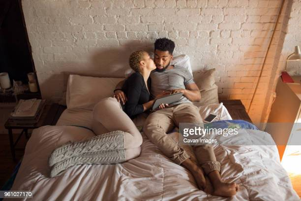 Overhead view of romantic woman kissing man while using tablet computer on bed
