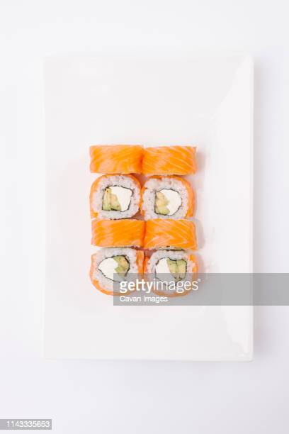 overhead view of salmon sushi rolls served in plate on white background - maki sushi stock pictures, royalty-free photos & images