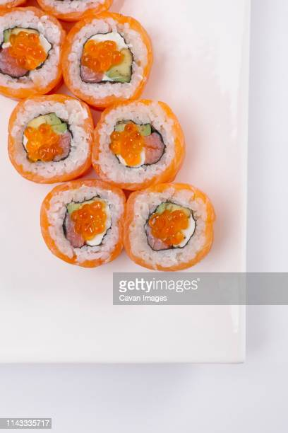 overhead view of salmon sushi rolls served in plate over white background - maki sushi stock pictures, royalty-free photos & images
