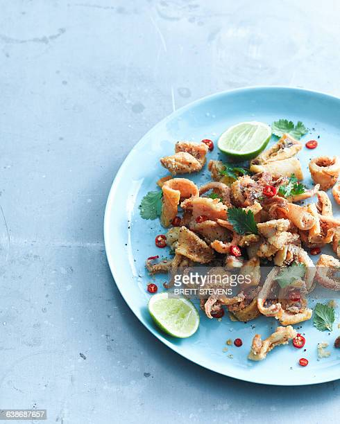 Overhead view of salt and pepper chilli squid garnished with lemon and coriander on plate