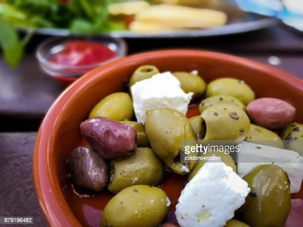 Vue de la sélection des olives noires et vertes à la feta dans le plat en terre cuite