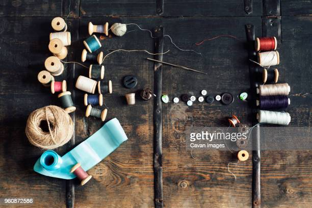 overhead view of sewing equipment with thread reels on wooden table - ribbon sewing item stock pictures, royalty-free photos & images