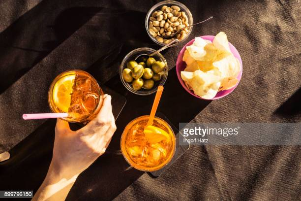 Overhead view of sidewalk cafe table with womans hand holding aperitif, Riccione, Emilia-Romagna, Italy
