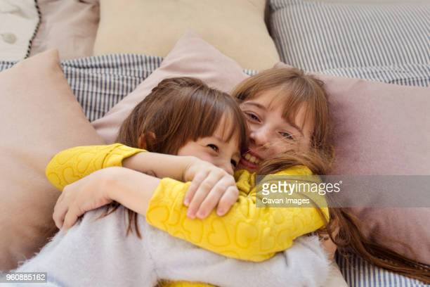 overhead view of sisters embracing while relaxing on bed at home - nur kinder stock-fotos und bilder
