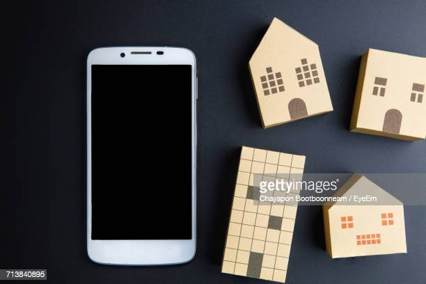 Overhead View Of Smart Phone With Model Houses On Table