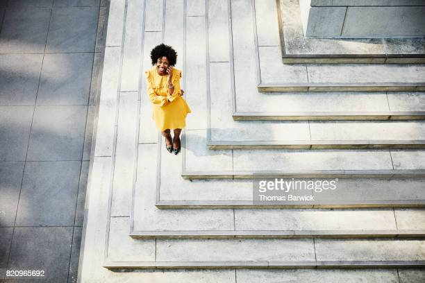 overhead view of smiling businesswoman talking on smartphone while standing on building steps - yellow dress stock pictures, royalty-free photos & images
