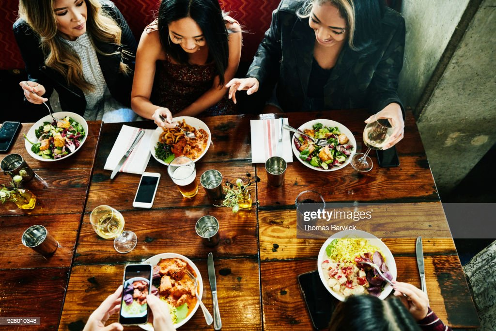 Overhead view of smiling female friends sharing lunch in restaurant : Stock-Foto