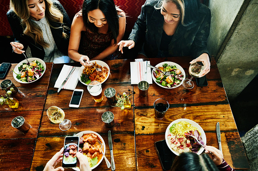 Overhead view of smiling female friends sharing lunch in restaurant - gettyimageskorea