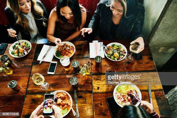 overhead view of smiling female friends sharing lunch in restaurant - almoço imagens e fotografias de stock