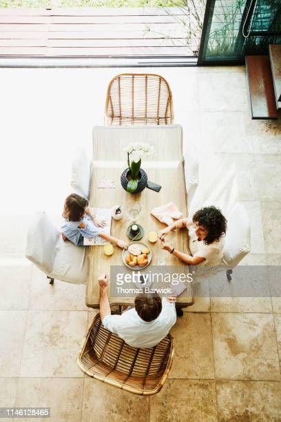 overhead view of smiling wife and husband sharing breakfast with daughter at dining room table - nosotroscollection stockfoto's en -beelden