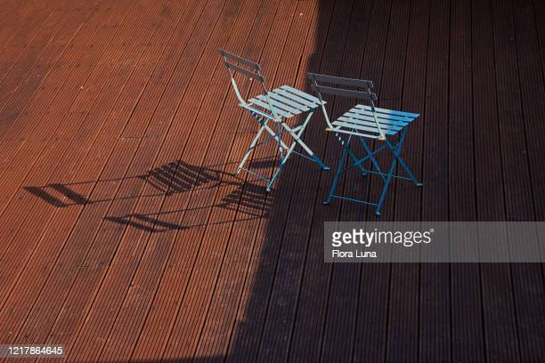overhead view of stained garden decking with 2 ciano garden chairs - chair stock pictures, royalty-free photos & images