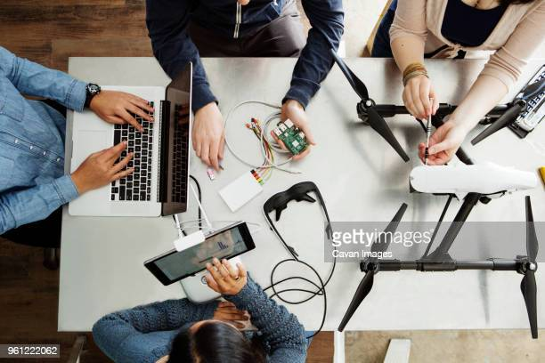 overhead view of students working on electrical equipment at table in classroom - computer repair stock pictures, royalty-free photos & images