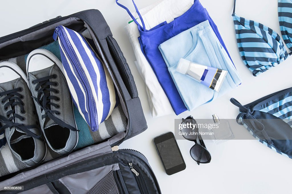 Overhead view of suitcase being packed for vacation : Stock Photo
