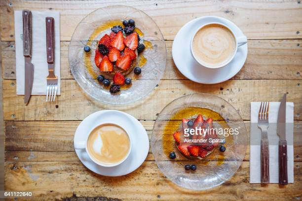 Overhead view of symmetric breakfast for two persons with pancakes and coffee