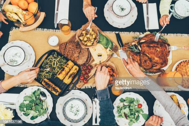 overhead view of table during christmas dinner - dinner table stock photos and pictures