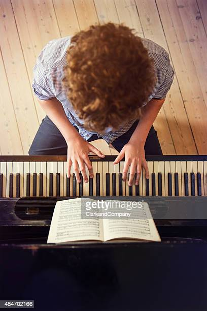 Overhead View of Teenage Boy Playing Piano In Sunlight Room