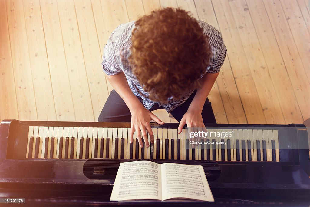 Overhead View of Teenage Boy Playing Piano In Sunlight Room : Stock Photo