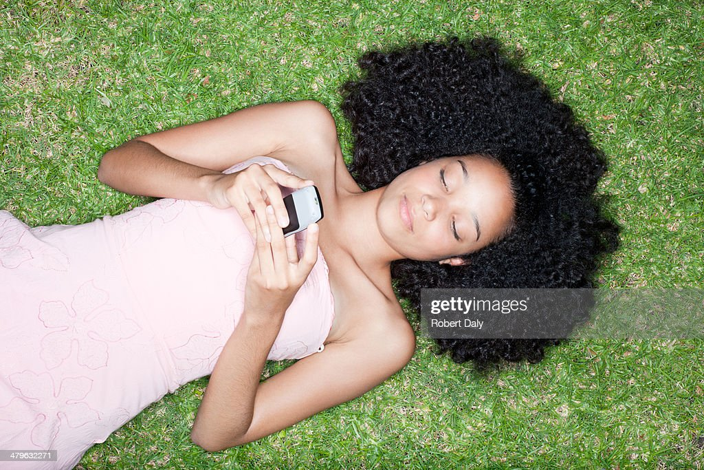 Overhead view of teenage girl laying on grass with cell phone : Stock Photo