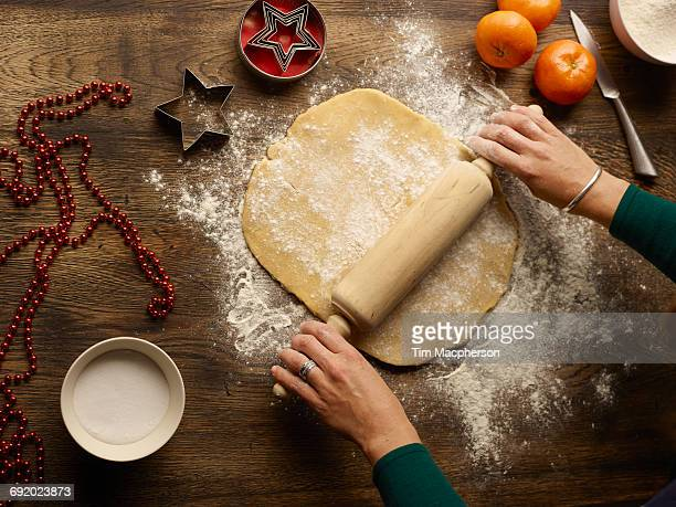Overhead view of teenage girls hands rolling christmas star biscuit dough