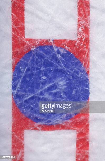 Overhead view of the face-off circle in the center of an ice hockey rink shows the scratches of use, late 20th Century.