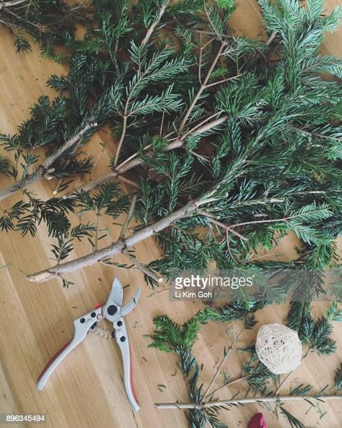 Overhead view of the mess from making Christmas wreath from leftover branches from a Christmas tree