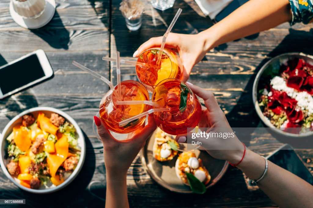 Overhead view of three women making a celebratory toast with aperol spritz cocktails : Stock Photo