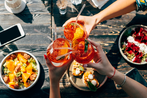 Overhead view of three women making a celebratory toast with aperol spritz cocktails - gettyimageskorea