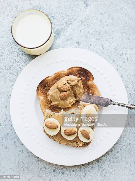 Overhead view of toast with almond butter, banana and milk