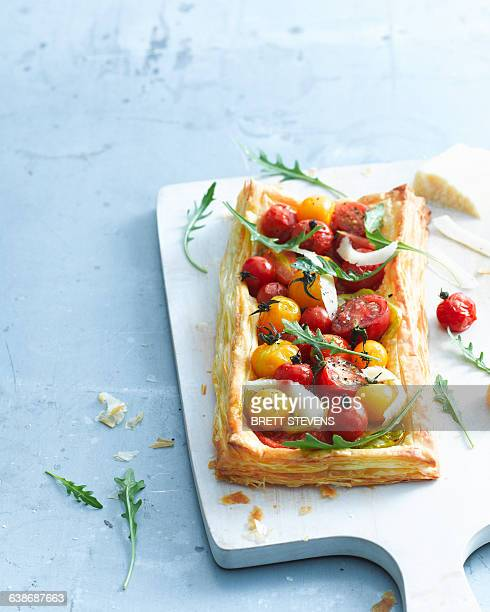 Overhead view of tomato and parmesan puff pastry tart garnished with rocket on cutting board