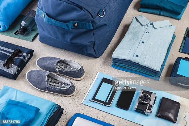 overhead view of travel packing with blue shirt, retro camera, training shoes, smartphone and notebook - neat stock pictures, royalty-free photos & images